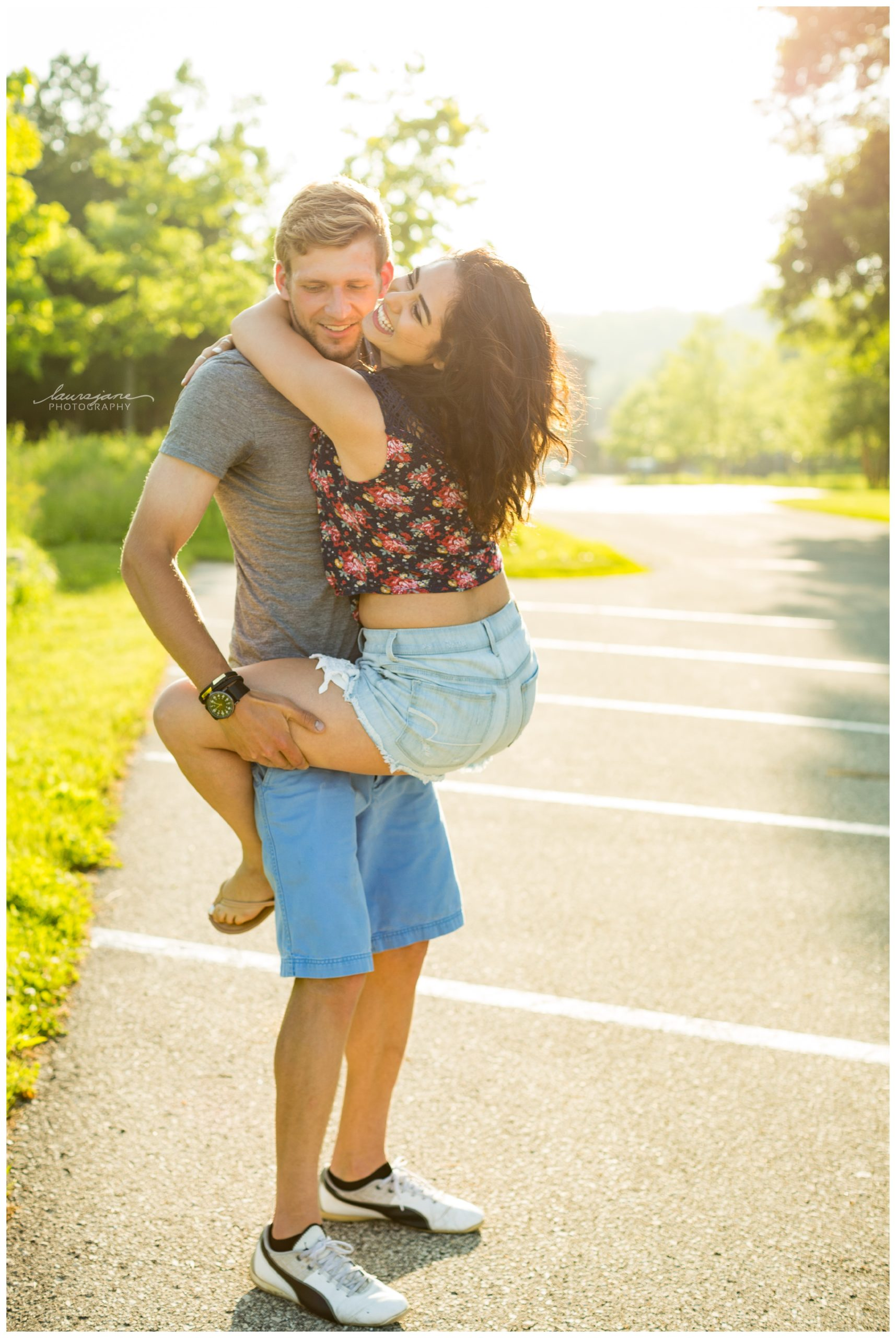 Playful engagement photo of woman hanging on her man